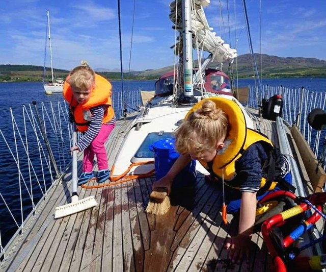 toddlers in life jackets cleaning their sailboat deck