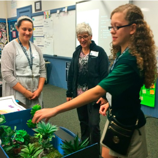 Student tour guide shows science project to visitors