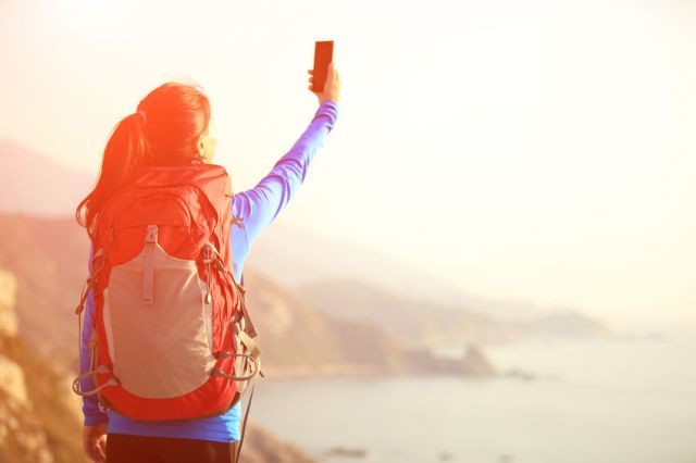 55258766 - woman taking photo with phone at mountain peak