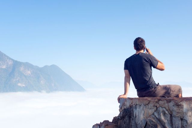 80155671 - man in travel in the mountains use mobile phone