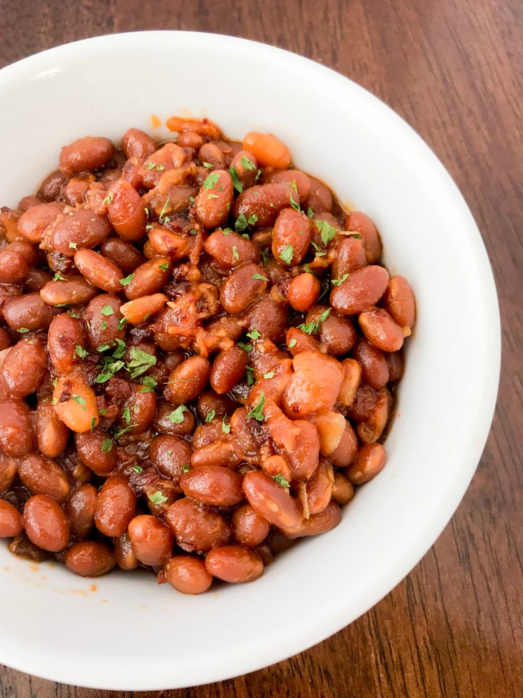 These Instant Pot BBQ Brown Sugar Baked Beans (pork and beans) may be one of the easiest recipes I've ever cooked. You literally just dump all of the ingredients into the Instant Pot and walk away. No fuss, no muss. This is an adaptation of my husband's crockpot beans, but instead of taking 6 hours to make, they only take an hour in the Instant Pot! #instantpotrecipe #bbqrecipe #brownbeans #porkandbeans #tailgating