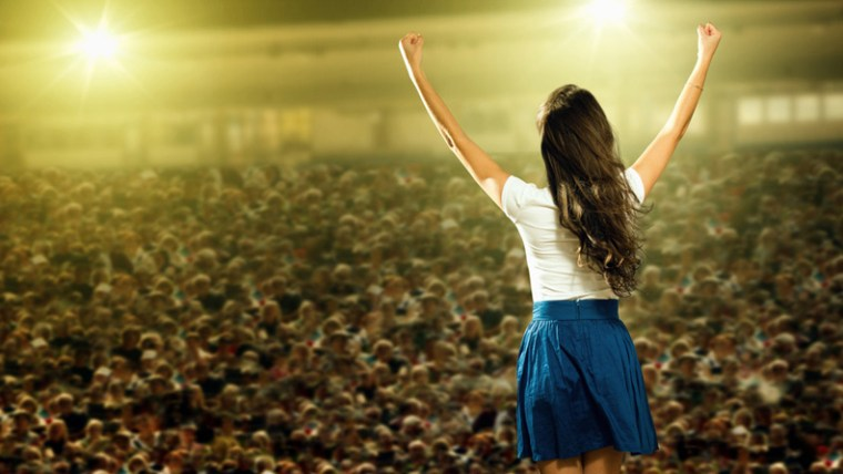 Woman With Arms Raised in front of Audience - Public Speaking Skills for Salespeople