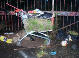 A discarded shopping kart filled with rubbish
