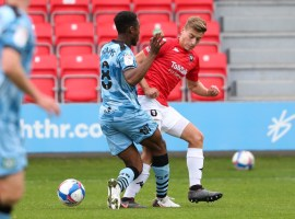 Golden getting the better of Forest Green Rovers midfielder, Ebrou Adams. Image courtesy of Salford City FC.