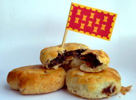 Eccles Cake, with the flag of Greater Manchester. Photo Credit: James Jones via Wikimedia Commons: https://commons.wikimedia.org/wiki/File:Eccles_Cake,_from_Greater_Manchester.jpg