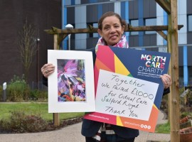 Artist Susan Aggarwal with one of her prints entitled 'A Rainbow of Flowers Our NHS', which she sold to help raise £1,000 for the Critical Care Unit at Salford Royal.