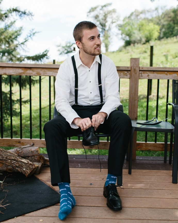 Groom sits to put on his shoes