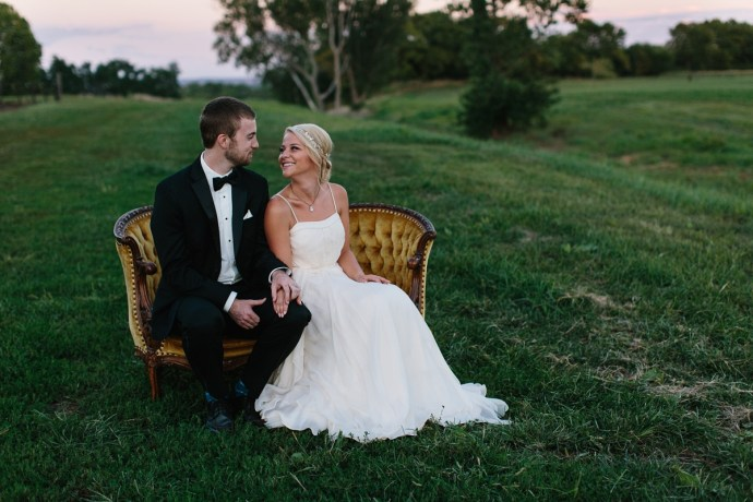 Bride and groom sit with each other on antique bench in an open field