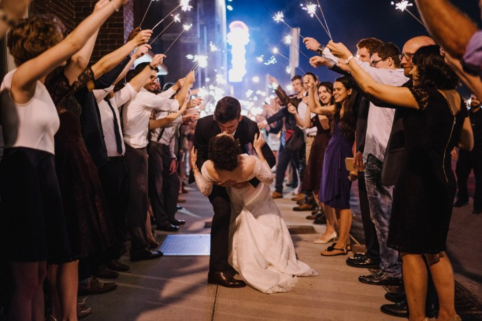 Bride and groom kiss under sparklers in city of Nashville