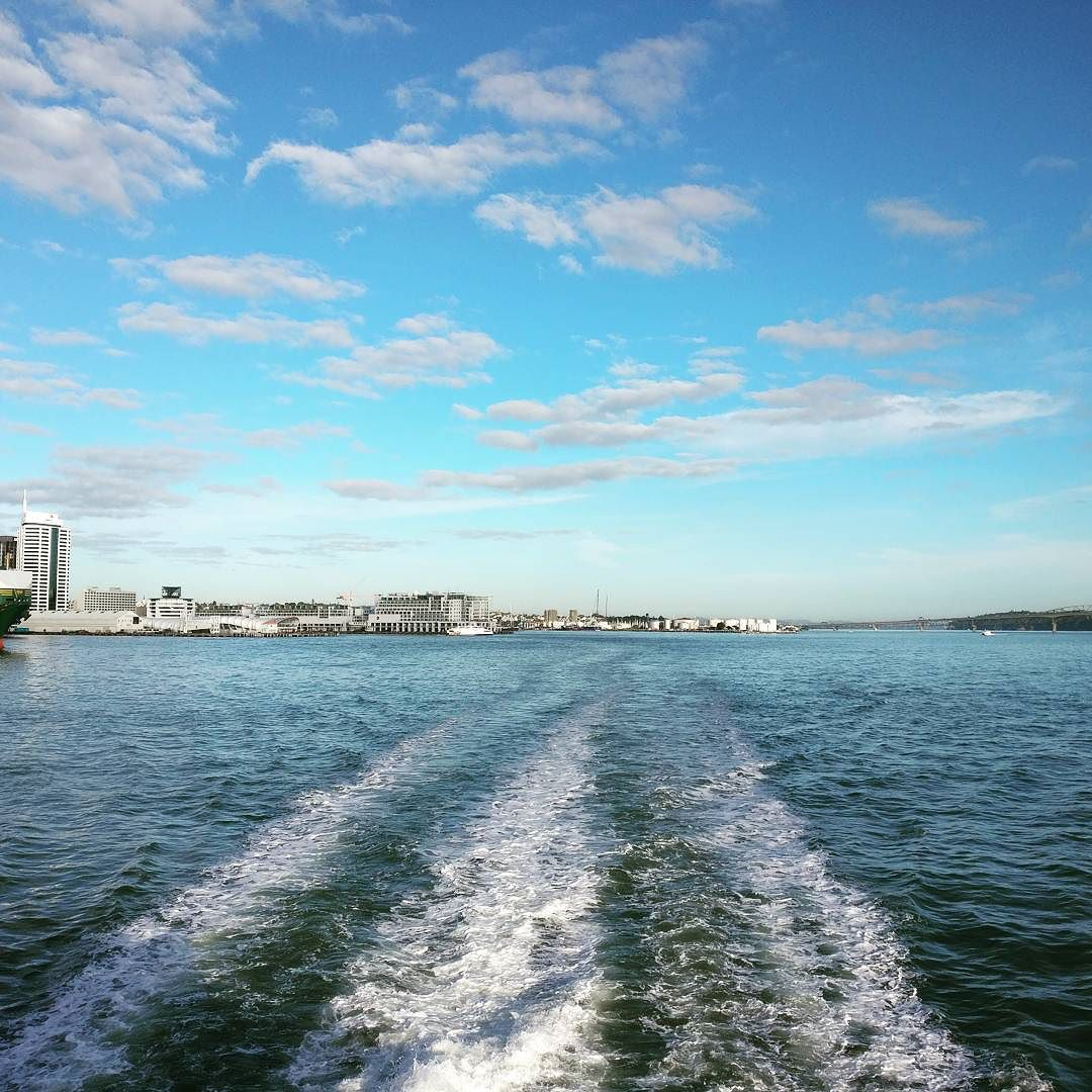 picture taken from the back of a ferry of Auckland Harbour heading to Waiheke Island. Turbulent water and blue skies.