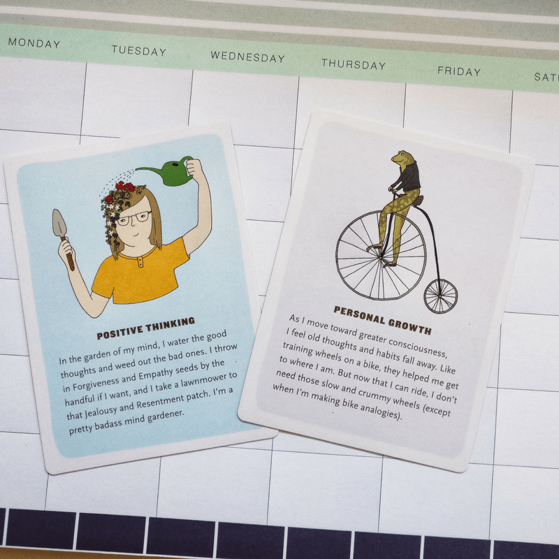 one card with a woman watering a garden on her head called positive thinking and a card with a frog on a penny farthing called personal growth. Both lying on a calendar with days of the week.