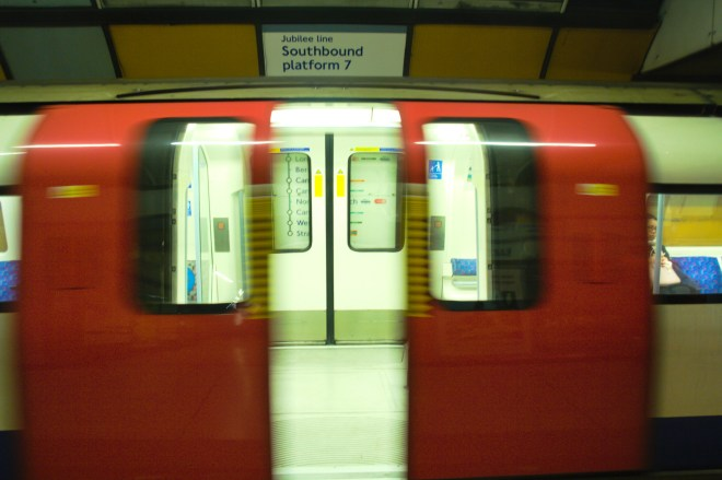 Photograph of the London Underground's Jubilee Line. The train's red double doors are directly in front and blurred as they are in the process of closing.