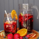 A pitcher and a large glass jar filled with sangria
