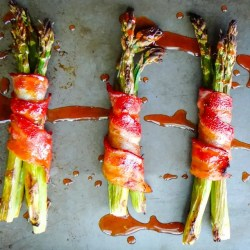 Image of 3 bundles of roasted asparagus on a metal sheet pan. The asparagus is wrapped in bacon and drizzled with a honey sriracha sauce.