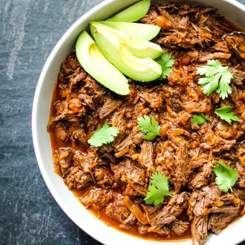 platter of shredded beef, topped with cilantro and avocado