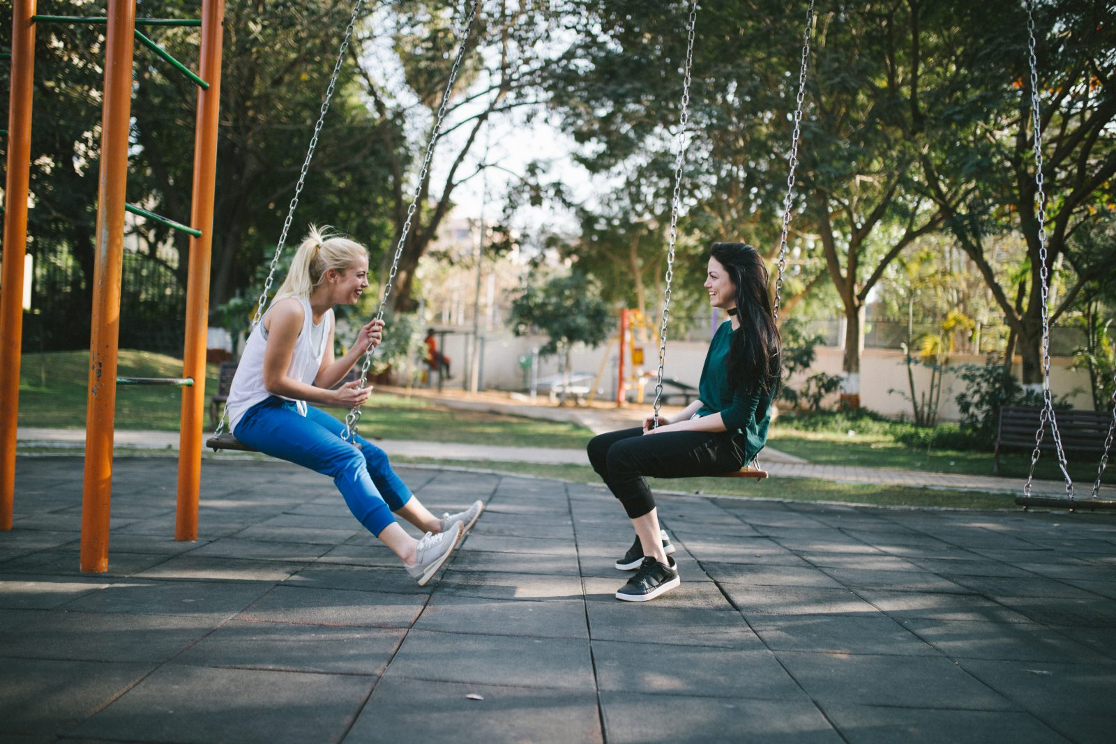 Two women laughing on swings