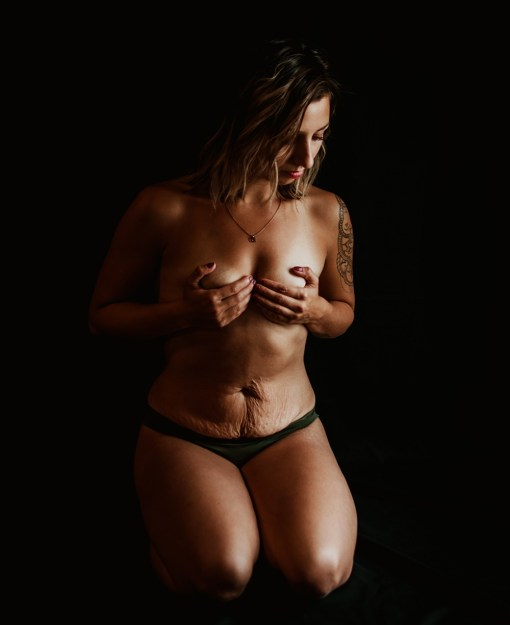woman wearing only underwear and covering her breasts with stretch marks on her stomach