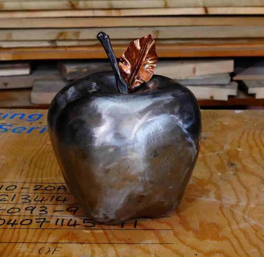 Forged steel apple made to force awareness of the hunger of 1/3 of the population