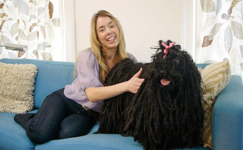 Woman and Puli dog on a couch