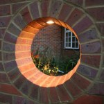 Garden wall with circular opening containing light