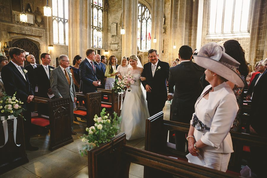 bride entering cirencester church by sam gibson