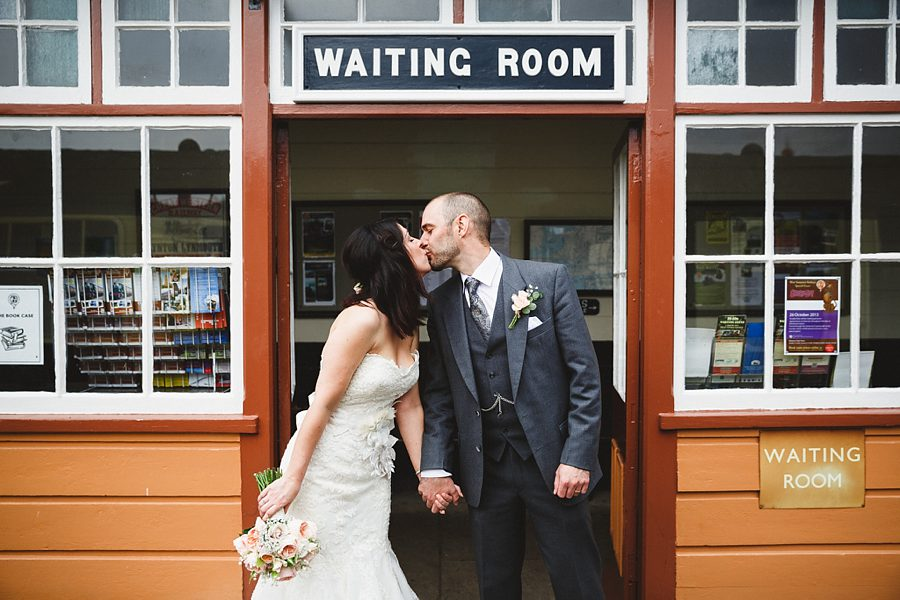 bride and groom kissing on a railway platform by sam gibson