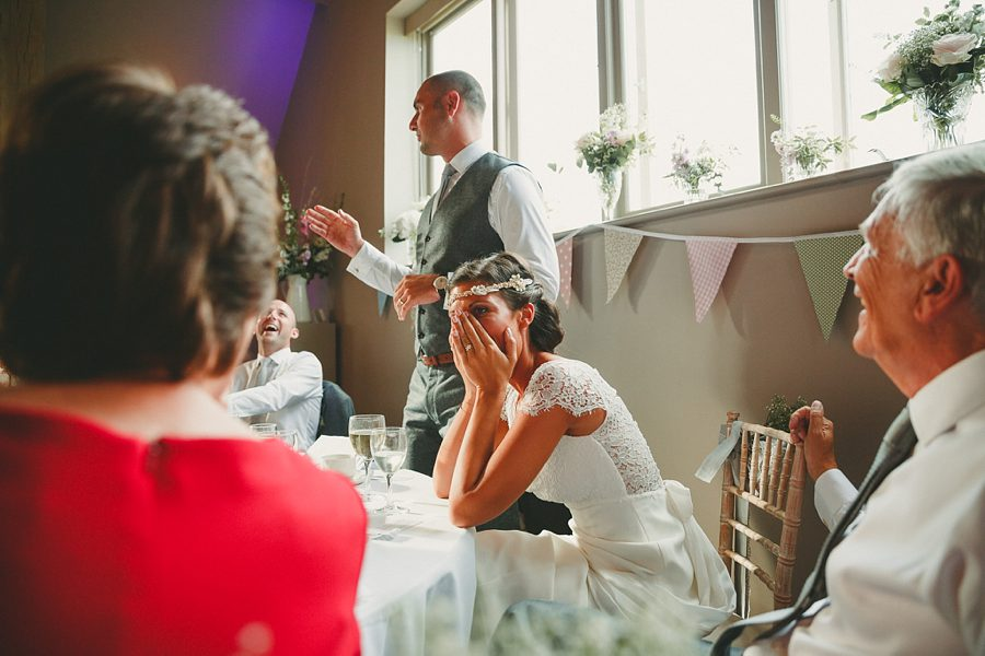 guests laugh during a speech at a wedding