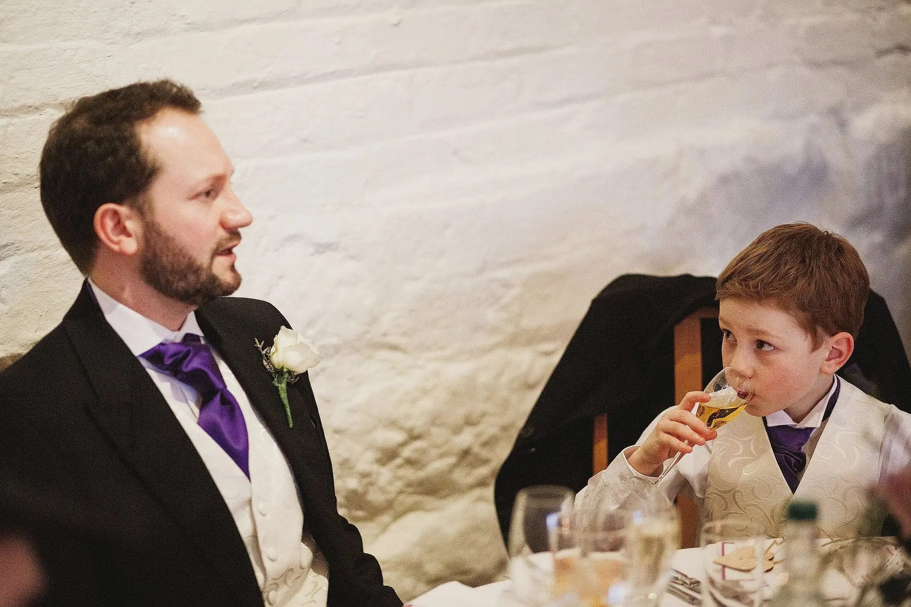 boy sips champagne at wedding