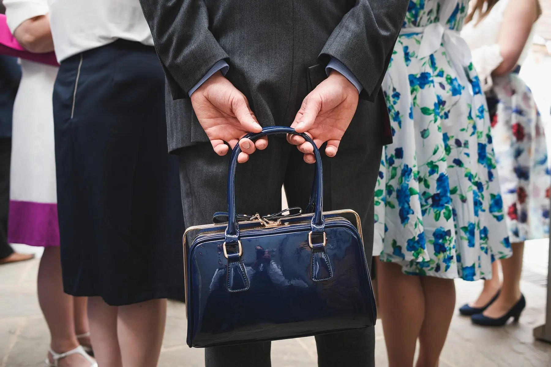 man holding handbag at a wedding