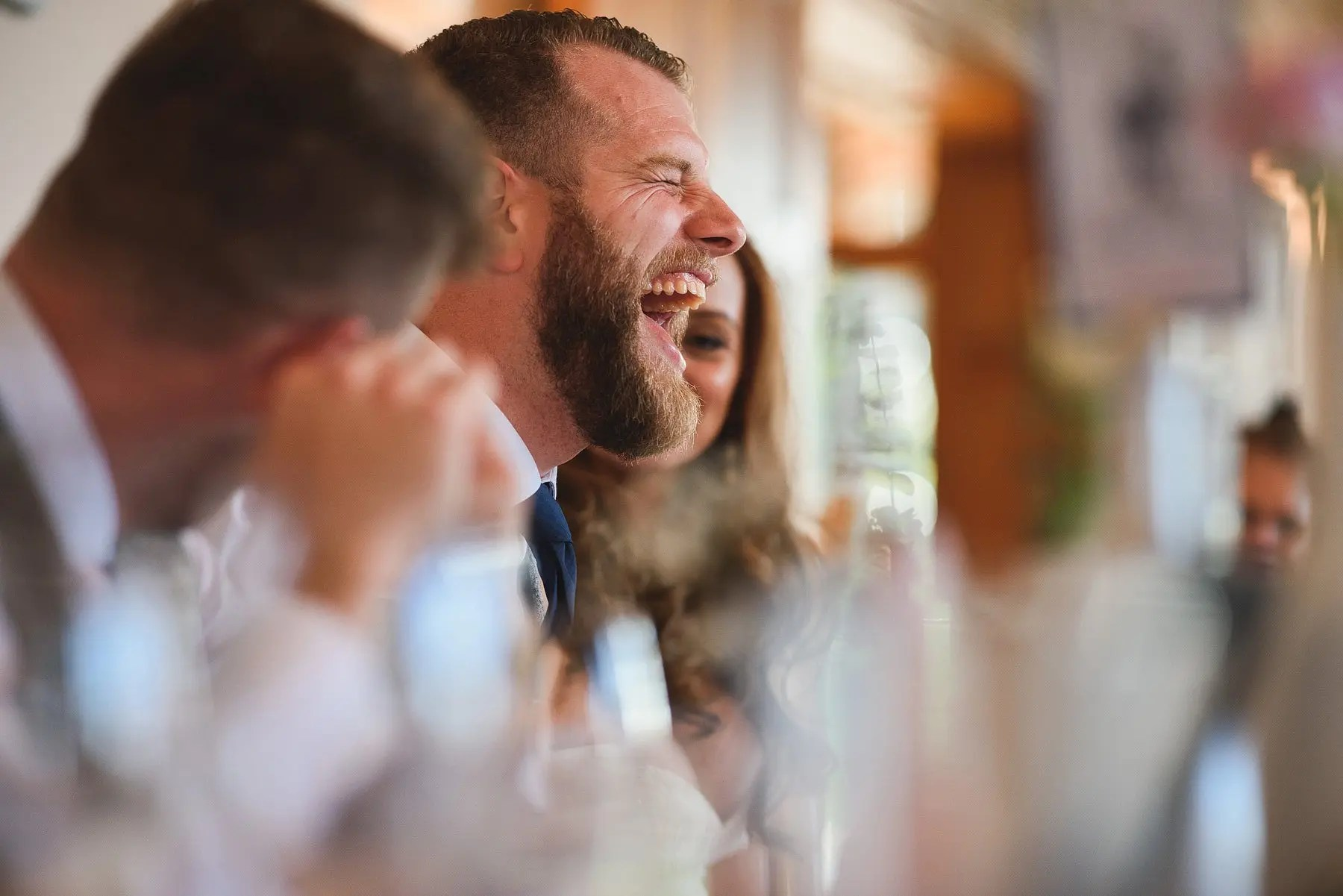 man laughing at wedding speech