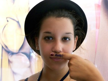 girl with moustache drawn on finger up to her nose