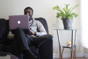 Samuel Osho with a Macbook creating content for numerous services