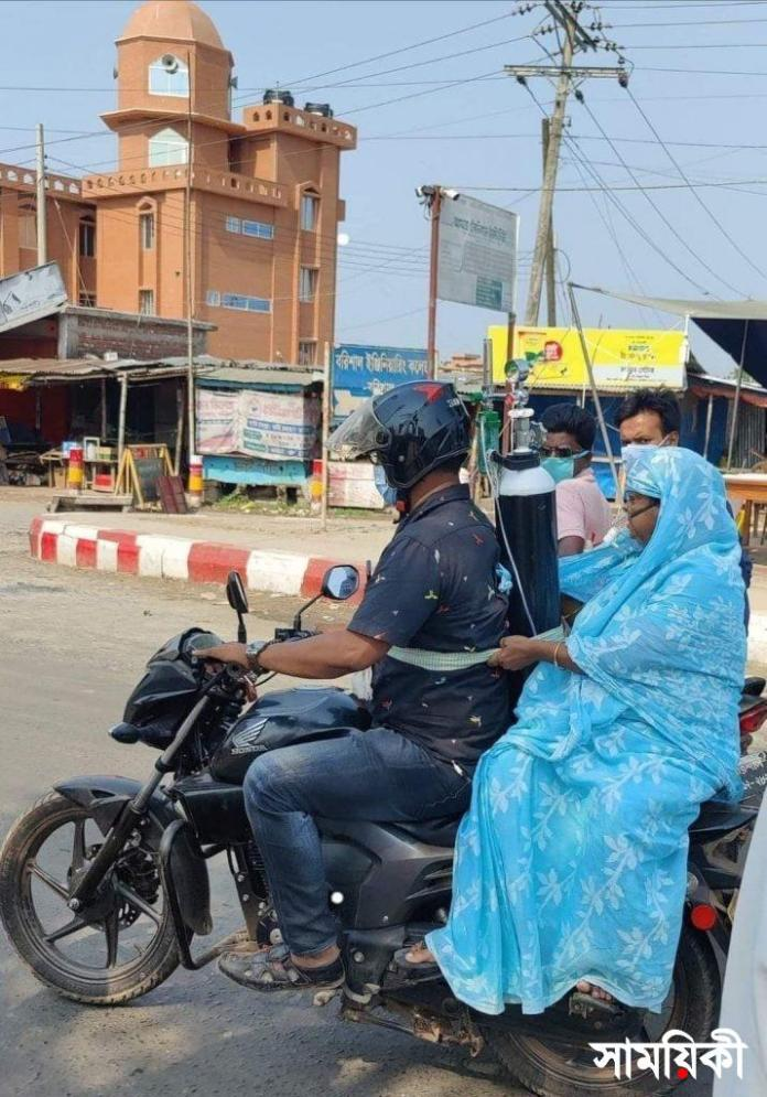Barishal to save mother son tiding oxigen cylender and driving her mother to Sher e Bangla Medical College hospital. photo collected with news বরিশালে স্বাস্থ্য সেবা নিশ্চিতে উচ্চ পর্যায়ে বৈঠক
