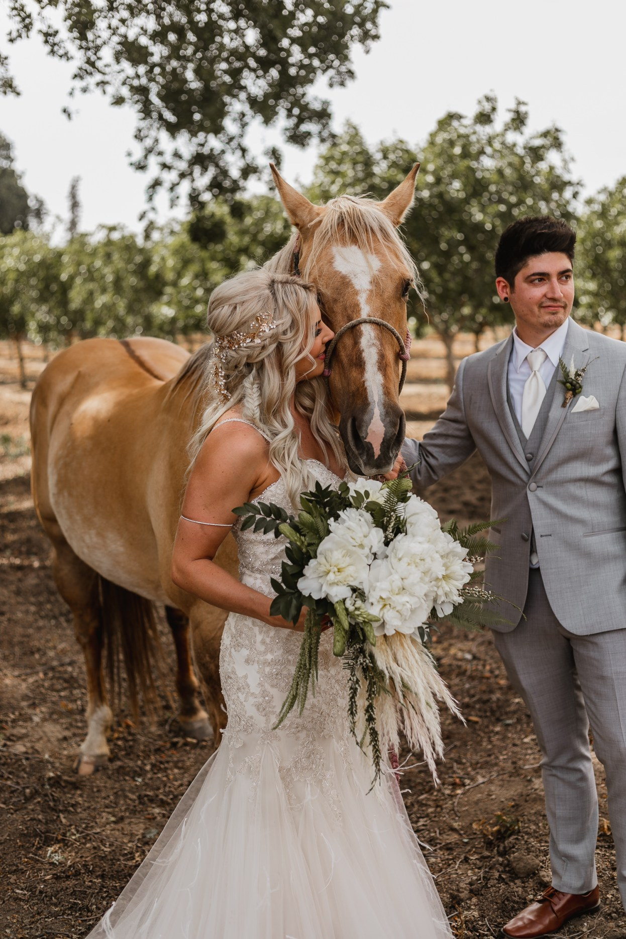 Bride and groom portraits with beautiful horse on ranch.