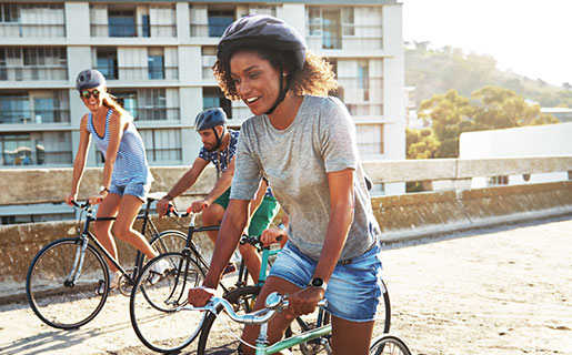 Two women and one man are riding bicycles together on a sunny day. They are similing and enjoying the ride while wearing Galaxy Watch 4 devices.
