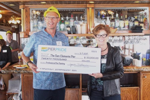 James Makshanoff, left, the city manager of San Clemente, receives a check for $20,000 from Julia Darden of San Clemente Pier Pride on Sunday, May 7, at the Fisherman's Restaurant & Bar. Photo: Courtesy of Dakota Ruiz