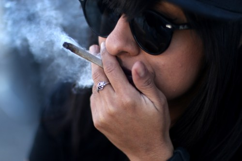 """A woman smokes from a cannabis cigarette, also known as a """"joint."""" New laws allow for personal use of recreational cannabis in California for people 21 and older, but federal laws and policies still classify cannabis in the top drug enforcement priority. Photo: Eric Heinz"""