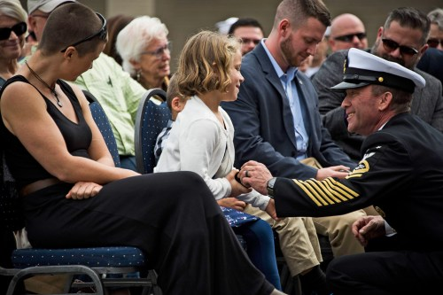 Decorated Navy SEAL Jason Gardner stepped down from the podium during his retirement speech to share a tender moment his wife and children among the audience. Photo: Courtesy of U.S. Navy