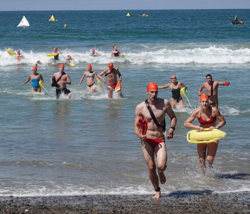 Surf rescue competitors make their way toward sbore. Photo: Fred Swegles