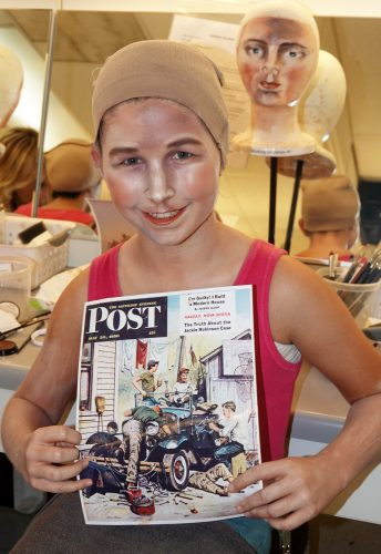 "San Clemente's Myla Pert, 11, gets her face painted, ultimately to look like the mannequin behind her, to appear in a Pageant of the Masters recreation of a painting titled ""Working on the Jalopy"" that once appeared on the cover of the Saturday Evening Post."
