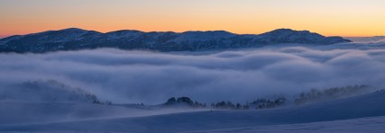 Clouds over the snow covered mountain range of the Vercors during dusk.
