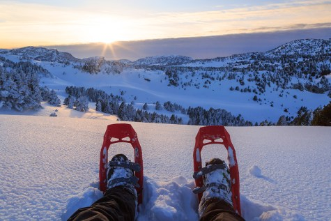 Hiker looking over his snowshoes at the sunset.