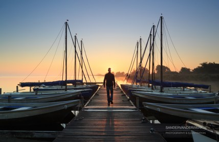 Man walking on a jetty during a foggy, autumn sunrise.