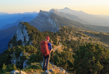 A hiker looking over the mountains just before sunset. Les Vercors, France.
