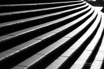 Black & White of modern, curved stairs in urban location.