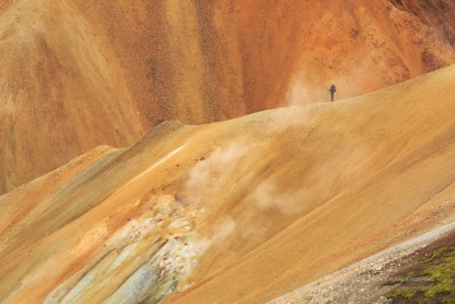 Hiker in the colorful mountains of Landmannalaugar.