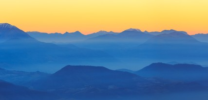 Colorful dusk in the French mountains, with the valley filled with fog.