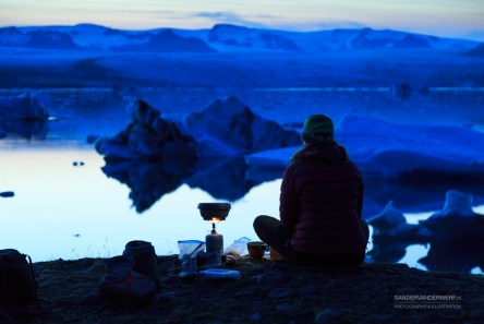 Female hiker cooking dinner at the Jokulsarlon lagoon on Iceland at dusk.