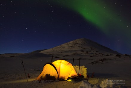 Aurora borealis, Northern Lights, over a tent in the snow in Sweden.