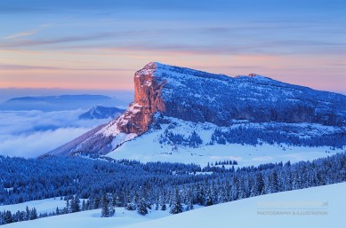 Winter forest on mountain range in French Alps during a colorful sunset.